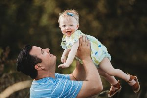 Outdoor family session of father with baby daughter.