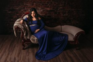 Maternity photo of woman on chaise lounge.