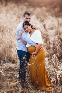 Pregnant woman posing for picture with husband.
