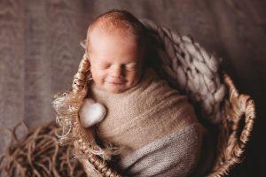 Studio photo of newborn smiling.