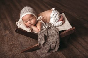 Photo of baby sleeping on a chair with blanket and bonnet.