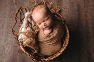 Studio photo of a newborn in a basket in studio.