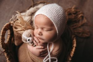 Studio photo of newborn in basket with stuffie and knit hat.