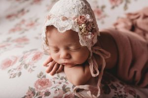 Studio photo of a newborn on a bed wearing a bonnet.