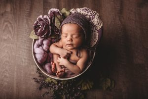 Photo of baby in decorated basket with wool hat.