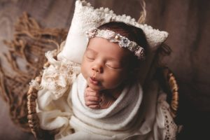 Photo of baby in a blanket and basket.