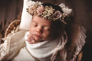 Photo of newborn in basket and blanket.