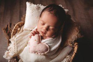 Photo of baby in basket on floor.
