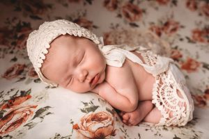 Photo of newborn on bed with bonnet.
