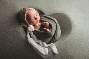 Photo of infant in blanket and bonnet.