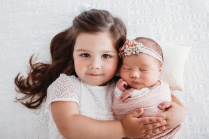 Photo of a baby with little sister.
